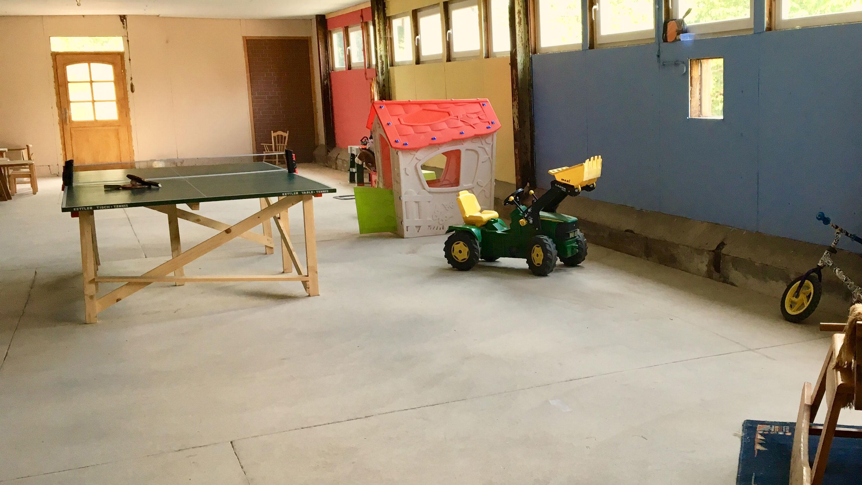 Spielhalle mit Fahrzeugen und Tischtennisplatte